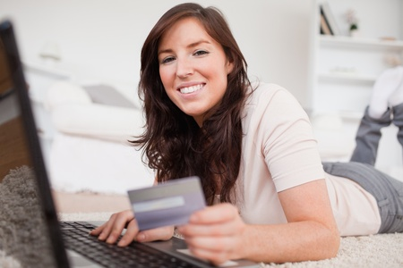 Young good looking female making a payment with a credit card on the internet while lying on a carpet in the living room photo