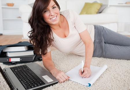 Young pretty woman relaxing with her laptop while writing on a notebook in the living room photo