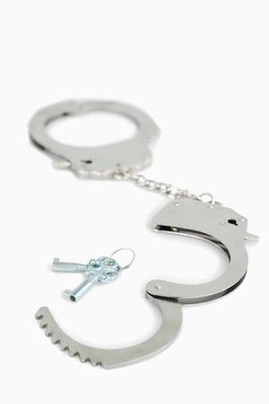 Handcuffs and keys against a white background photo