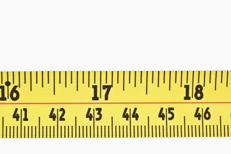 Close up of a part of a yellow measuring tape against a white background photo