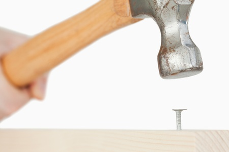 Hand holding a hammer to drive a nail into a wooden board with the camera focus on the nail photo