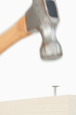 Close up of a hammer driving a nail against a white background Stock Photo - 10069640