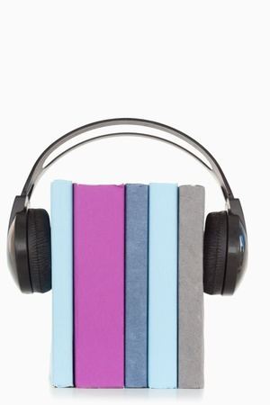A stack of books and headphones against a white background photo
