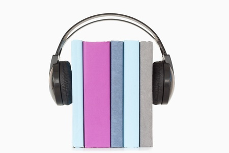 Close up of books and headphones against a white background photo