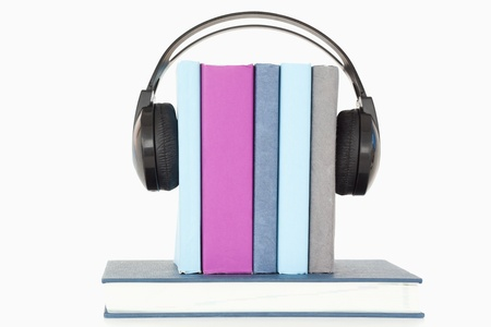 Headphones around books against a white background photo