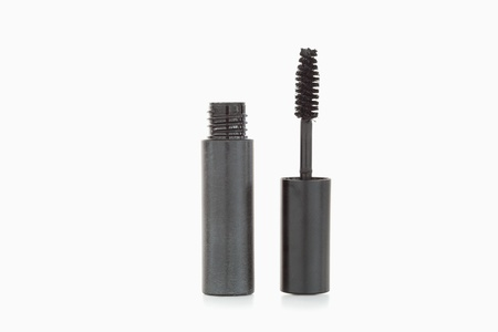 A black mascara brush and tube against a white background photo