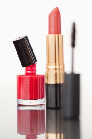 A mascara tube with a pale red lipstick and a red nail polish flask against a white background photo