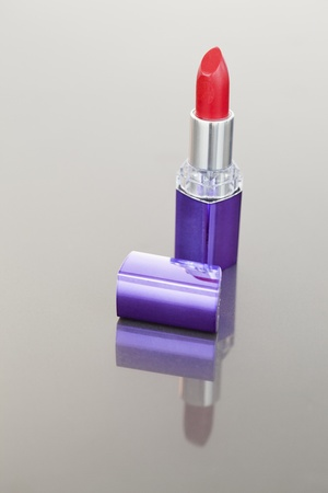 Portrait of a red lipstick with a purple tube against a white background photo