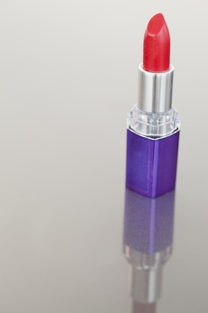Portrait of a lipstick with a purple tube against a white background photo
