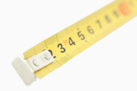 Camera focus on a yellow measuring tape against a white background photo