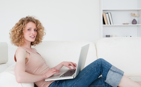 Attractive blonde woman relaxing with her laptop while sitting on a sofa in her appartment Stock Photo - 10069818