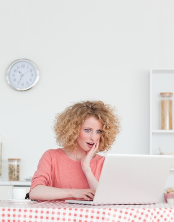 Charming blonde female relaxing with her laptop while sitting in the kitchen in her appartment photo