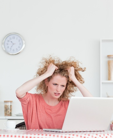 Attractive blonde female being angry while relaxing with her laptop in the kitchen in her appartment Stock Photo - 10070129