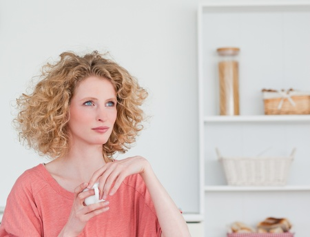 Attractive blonde woman drinking a cup of coffee while sitting in the kitchen in her appartment photo