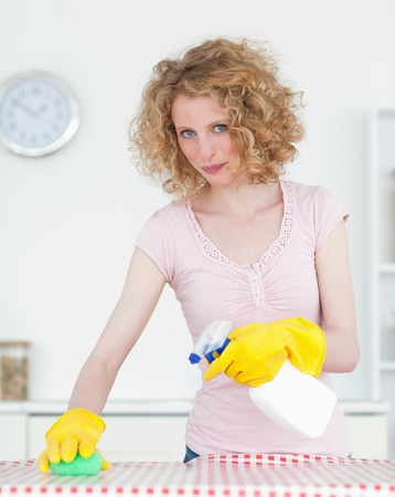 Pretty red-haired woman cleaning a cutting board in the kitchen in her apartment  photo