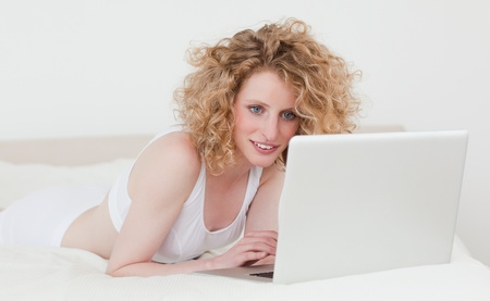Good looking blonde woman relaxing with her laptop while lying on her bed in her appartment photo