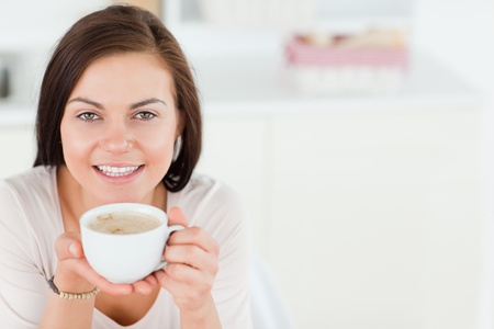 Smiling dark-haired woman having a coffee in her kitchen photo