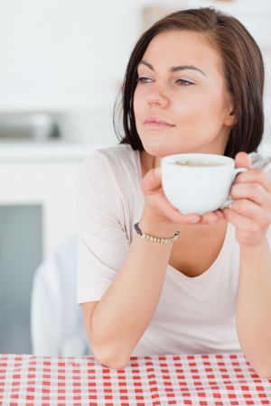 Portrait of a smiling dark-haired woman having a coffee in her kitchen photo