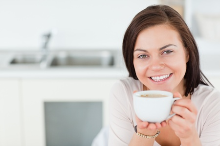 Close up of a smiling brunette having a coffee in her kitchen photo