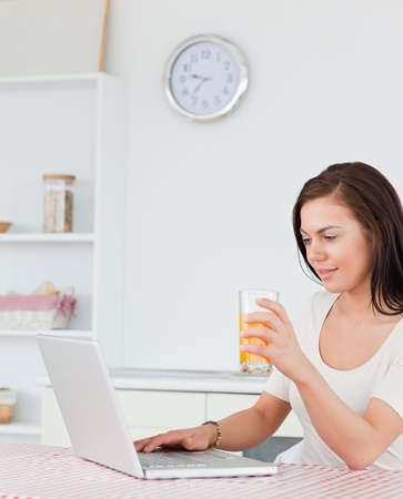 Portrait of a woman using her laptop and drinking juice in her kitchen photo