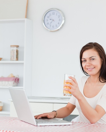 Portrait of a brunette using her laptop and drinking juice in her kitchen photo