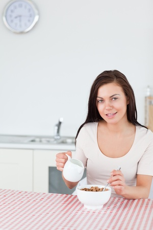 Portrait of a young woman pouring milk in her cereal in her kitchen photo