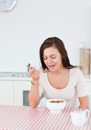 Cute woman eating cereal in her kitchen Stock Photo - 10071427
