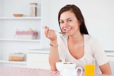 Beautiful woman eating her cereal in her kitchen Stock Photo - 10074146