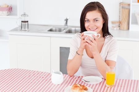 Charming brunette having her breakfast in her kitchen photo