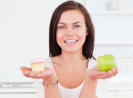 Young woman with an apple and a piece of cake against a white background photo