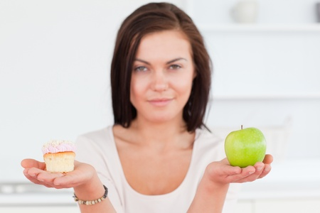 Charming brunette with an apple and a piece of cake looking at the camera photo