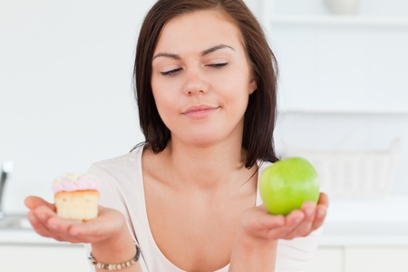 Close up of a cute brunette with an apple and a piece of cake looking at the apple photo