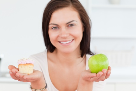Close up of a cute woman with an apple and a piece of cake looking at the camera photo