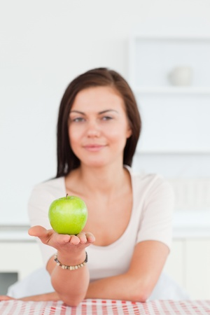 Young woman showing an apple with the camera focus on the fruit photo