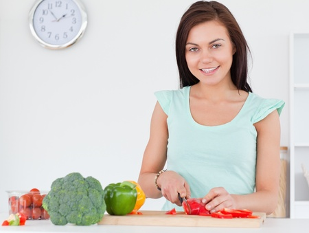 Woman slicing a pepper while looking at the camera in her kitchen photo