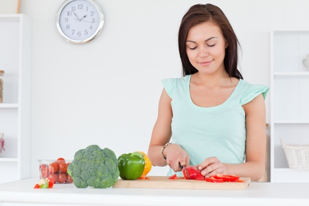 slicing: Cute woman slicing a pepper in her kitchen Stock Photo