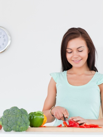Smiling woman slicing a pepper in her kitchen photo