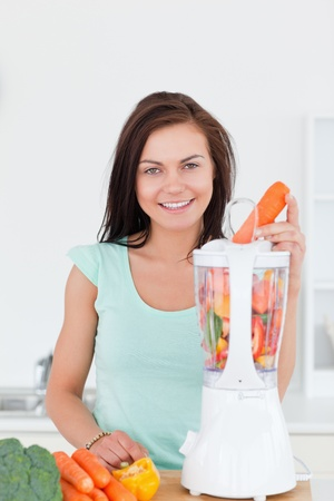 Young woman using a blender in her kitchen photo