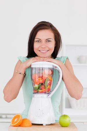 licuadora: Joven sonriente posando con una batidora en su cocina Foto de archivo