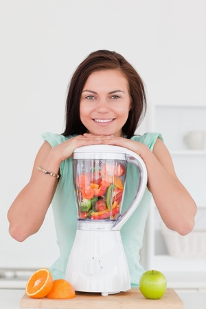 Smiling young woman posing with a blender in her kitchen