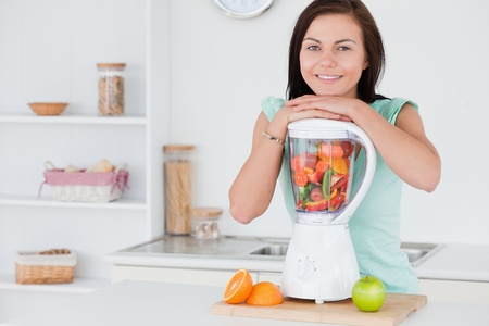 Brunette posing with a blender while looking at the camera photo