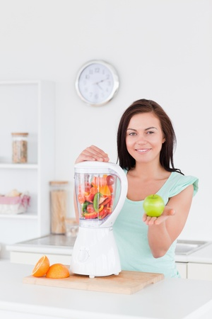 Cute woman with a blender and an apple while looking at the camera photo