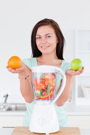 Happy woman with a blender and fruits while looking at the camera photo