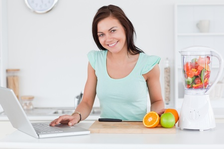 Cute brunette with a laptop and fruits in her kitchen photo