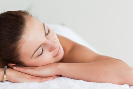 massage table: Close up of a young brunette lying on a massage table in spa