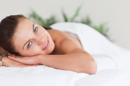 Close up of a cute woman lying on a massage table looking at the camera photo