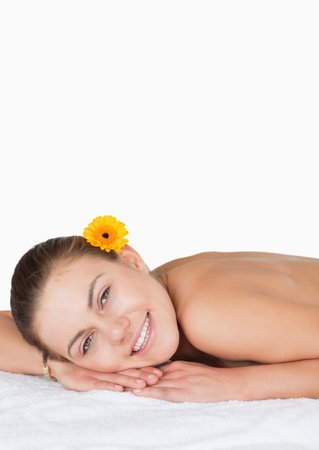 Portrait of a dark-haired woman with a flower on her ear in a spa photo