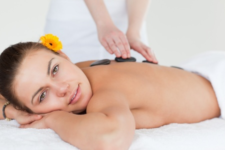 Close up of a delighted woman having a hot stone massage while looking at the camera photo