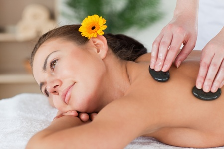 Close up of a cute woman enjoying a hot stone massage in a spa photo