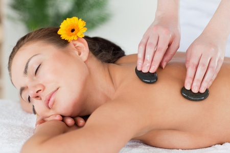 head stones: Close up of a beautiful woman enjoying a hot stone massage with a flower on her ear Stock Photo